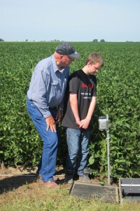 A farmer and his son examining an implement designed to control water levels and reduce nutrient runoff from the corn fields.
